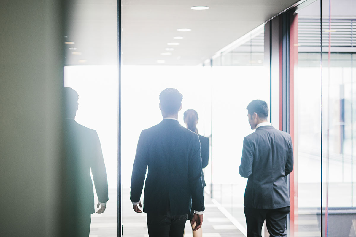 Group of business men and women walking through modern office in the distance with all their backs facing photo