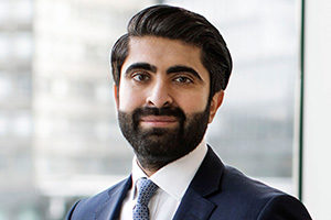 head shot of Head of Commercial Litigation and lawyer solicitor Harshiv Thakerar standing and posing for photo in formal business suit while smiling in Augusta London offices