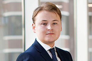 head shot of Augusta Business man dressed in suit investment associate in the diligence team Angus Sinclair standing and posing for photo with a smile in bright modern London office.