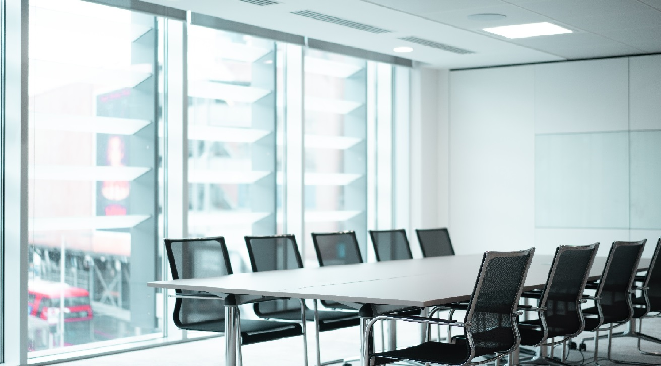 modern Augusta Litigation funding London office boardroom with long table and align chairs during the day with bright large floor to ceiling windows in the background