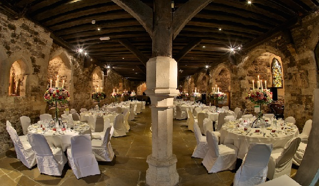 Underground crypt banquet hall with several round tables and chairs with white coverings