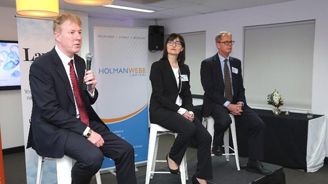 panel of 3 business people adressing crowd with managing partner Neill Brennan holding microphone and talking