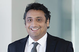 head shot of Augusta Business man dressed in suit Investment Manager and lawyer kedar vishwanathan standing and posing for photo with a smile in bright modern Sydney Australia office room.