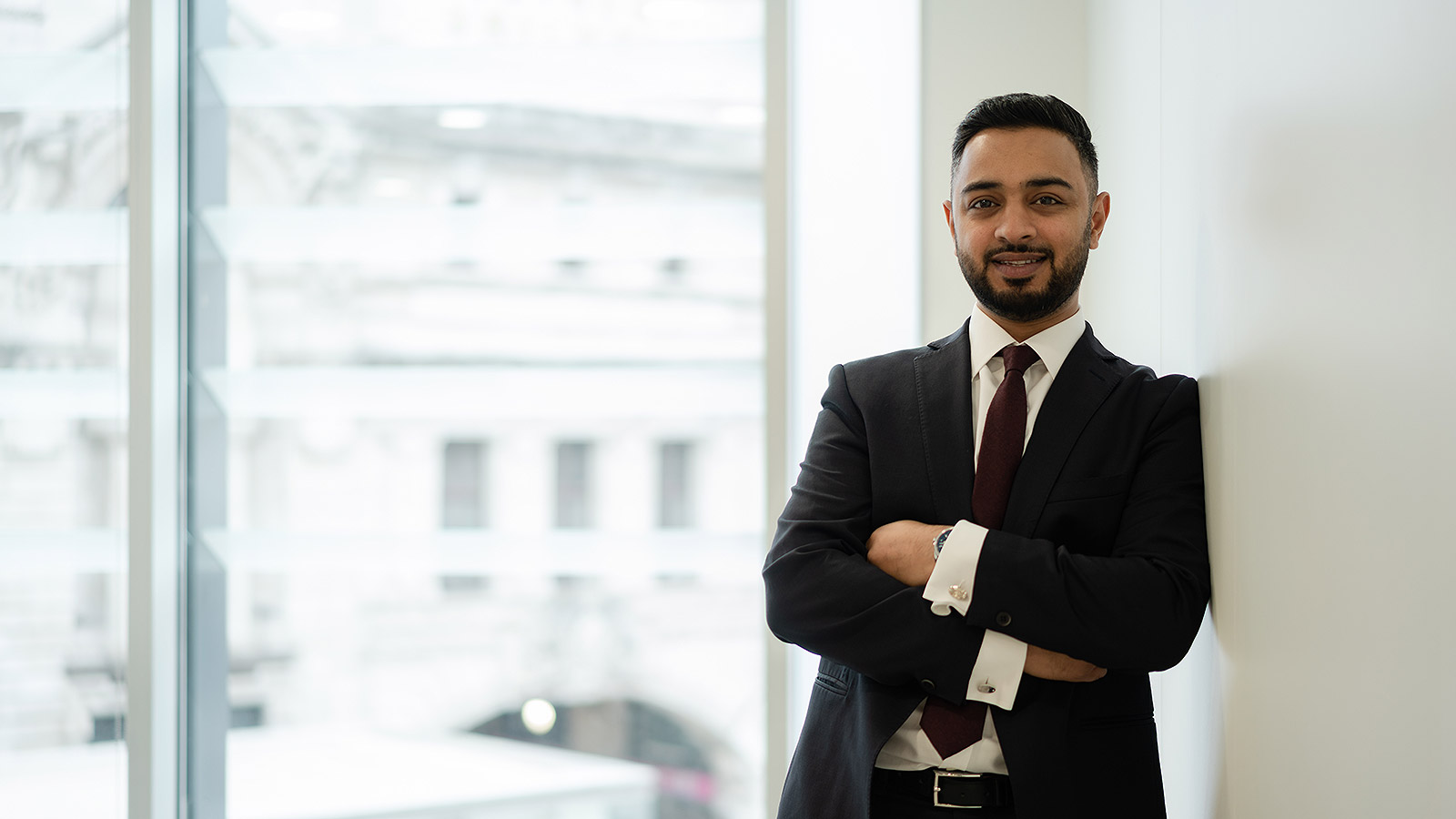 Augusta Business man dressed in suit head of originations and lawyer Mohsin Patel standing and posing for photo with a smile in bright modern London office room next to wide and floor to ceiling windows
