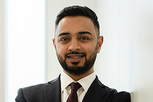 head shot of Augusta Business man dressed in suit head of originations and lawyer Mohsin Patel standing and posing for photo with a smile in bright modern London office room next to wide and floor to ceiling windows