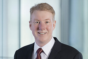 head shot of Augusta Business man dressed in suit managing director and founding partner Neill Brennan standing and posing for photo with a smile in bright modern Sydney Australia office room.
