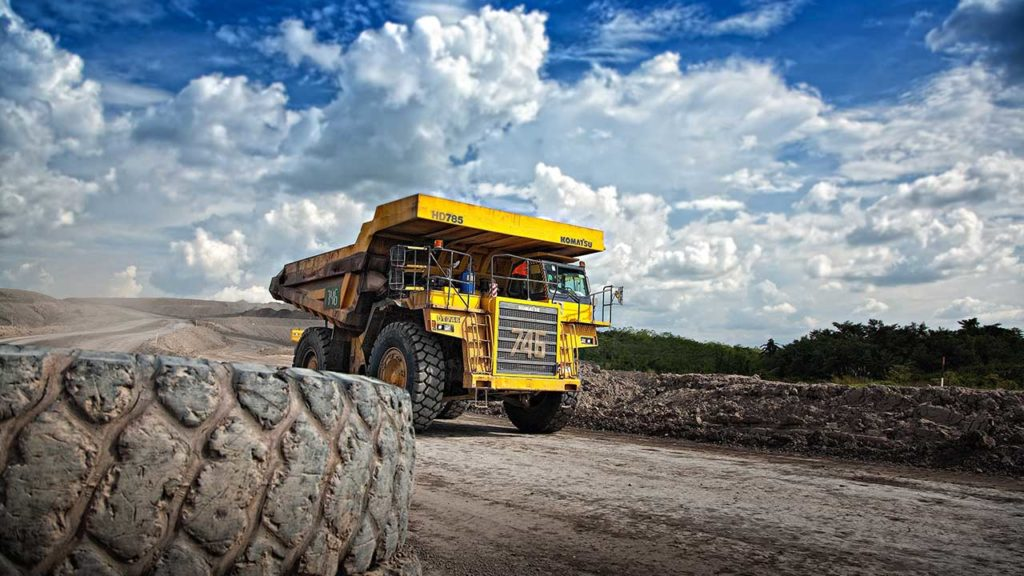 Mining truck driving through desolate landscape