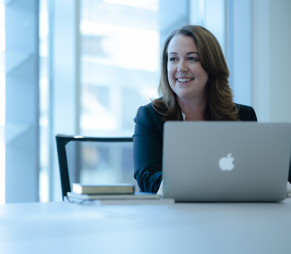 Head of group actions business women and investment manager Jac Young sitting behind an apple laptop smiling in Augusta London Office