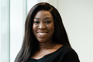 head shot of Augusta Business women dressed in formal clothes investment associate Yetunde Ogunbiyi, smiling, holding hands and posing for photo in bright modern London office room next to wide and floor to ceiling windows