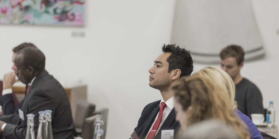 Investment manager and business man Simon latham listening to a lecture at an event in crowd of people