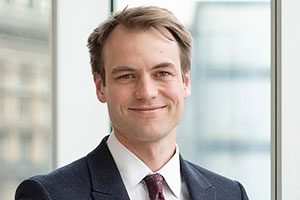 Head Shot of Augusta Business man dressed in suit Investment manager in the diligence team Andrew Roberts standing and posing for photo in bright modern London office room next to wide and floor to ceiling windows
