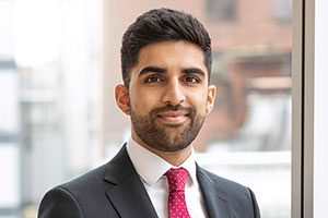 Head shot of Augusta Business man dressed in suit Financial Analyst Ehsan Nazir standing and posing for photo in bright modern London office room next to wide and floor to ceiling windows