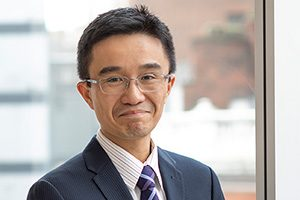 Head shot of Augusta Business man dressed in suit Financial controller Henry Ma standing and posing for photo in bright modern London office room next to wide and floor to ceiling windows