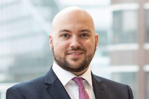 Head shot of Augusta Business man dressed in suit Head of recruitment Jared Glazier standing and posing for photo in bright modern London office room next to wide and floor to ceiling windows