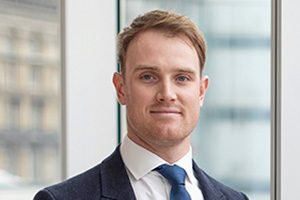 Head shot of Augusta Business man dressed in suit project manager Michael Taggart standing and posing for photo in bright modern London office room next to wide and floor to ceiling windows