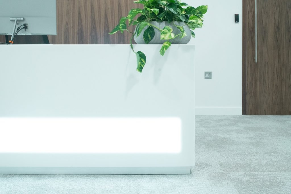 modern London office of reception desk with plan placed next to computer and desk light