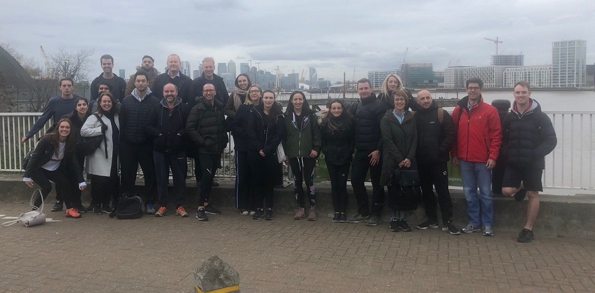 group photo of London Augusta staff standing next to river during a cold and foggy day