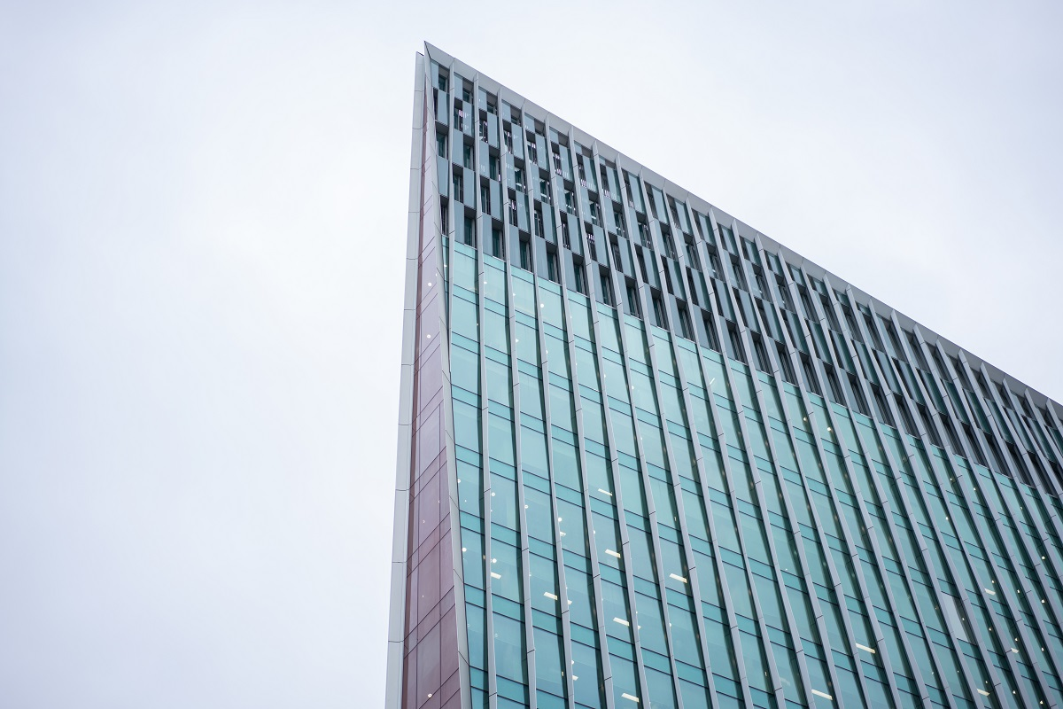 Modern triangular shaped tall building with long thin triangle face with blue glass windows either side with shot looking up to sky