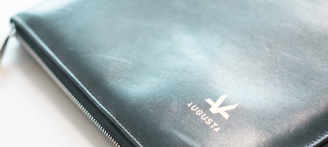 Black leather business folder with small orange Augusta logo in the corner close up view on a grey boardroom table