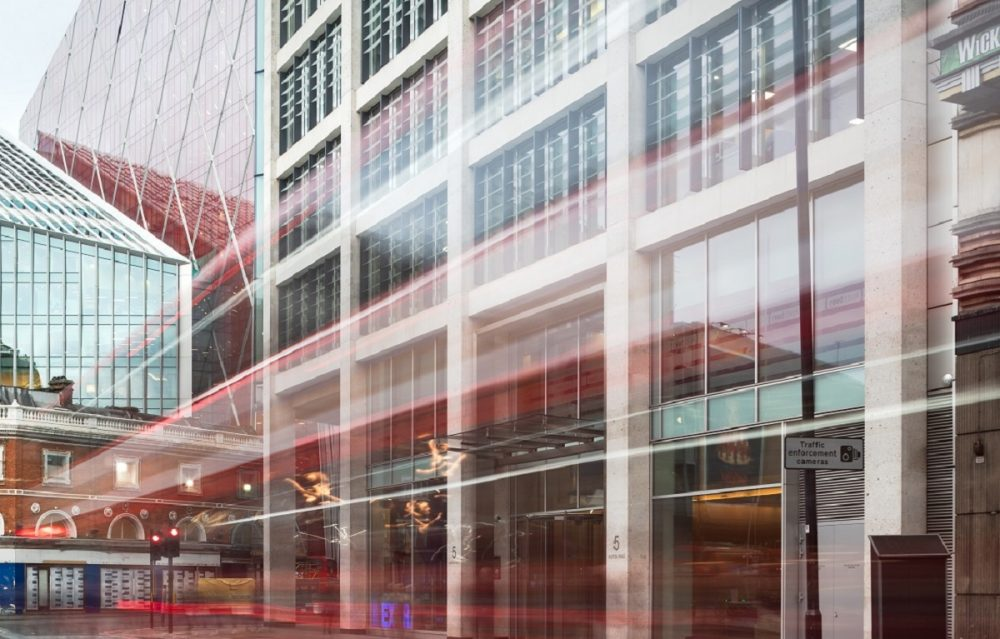 Exterior view of modern Augusta litigation funder's office buildings in London from street view and the red strips from London double Decker buses