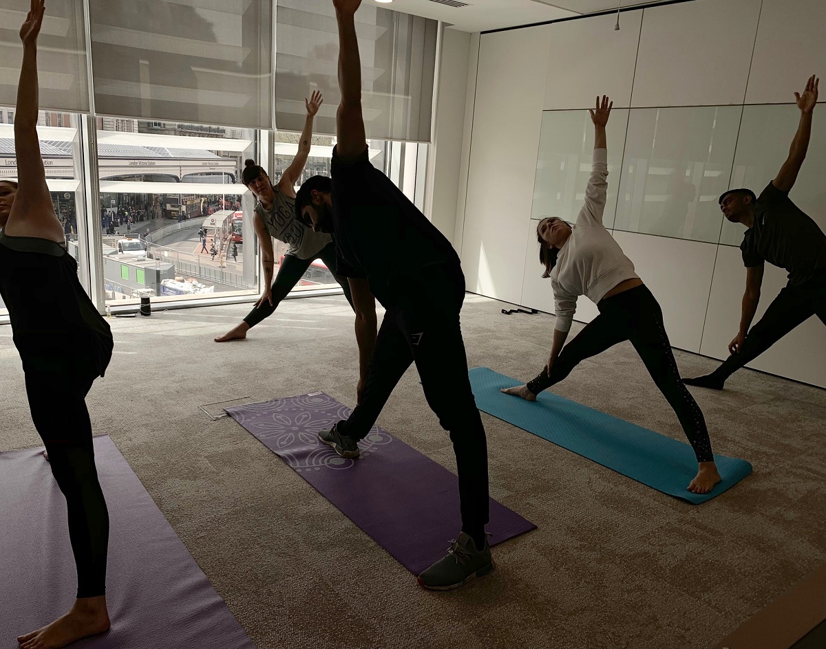 Group of people doing yoga stretches in Augusta London offices with Yoga teacher leading the class
