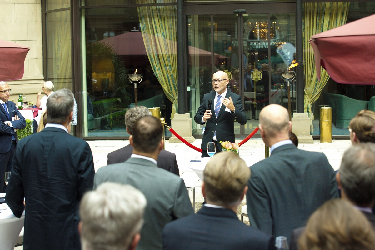 Business man standing in distance next to red velvet rope speaking and addressing a crowd of business people at an outside networking event in Germany