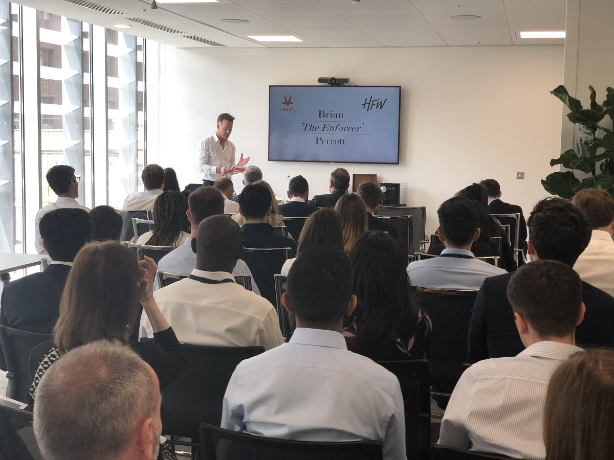 Partner of international law firm Brian Perrott presentation and speaking to a large crowd of Augusta staff in the Augusta London office while standing next to a large TV presentation