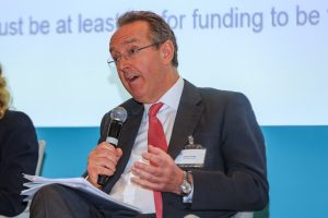 Augusta Litigation funding head of international arbitration and solicitor James Foster speaking and presenting to a crowd of people on a panel event