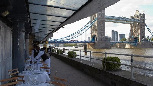Themes river and Tower bridge off in the distance with row of restaurant tables being prepared in the foreground with waiter attending to them