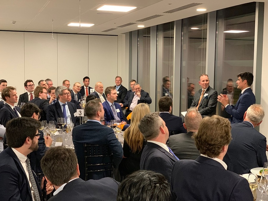 Modern Augusta Litigation Funder boardroom filled with 50 people sitting around round tables while listening to former England Cricket captain Alistair Cook speaking during a night time event