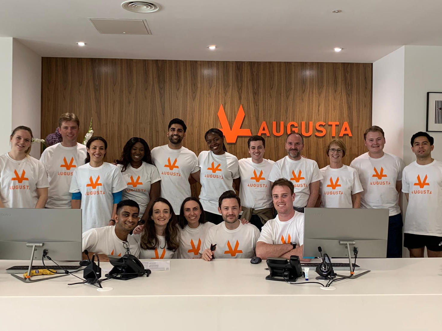 Group photo of 16 members of the Augusta staff lined up in Augusta London office with the orange Augusta Logo in the background smiling and posing for picture with the same Augusta branded T-Shirt