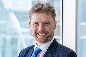 head shot of Augusta Business man dressed in suit Investment manager and lawyer in the structured projects team Oliver Lawson standing and posing for photo in bright modern London office room next to wide and floor to ceiling windows