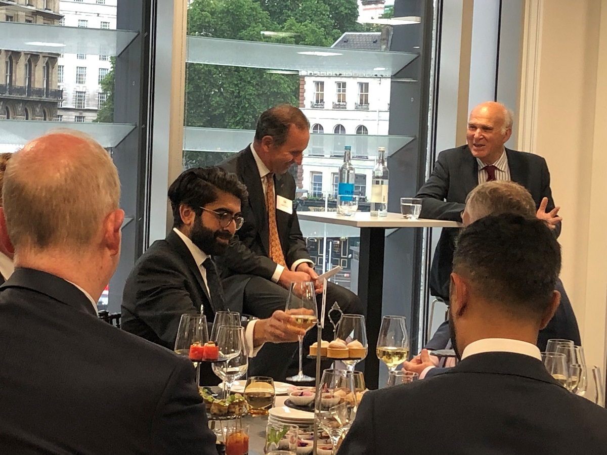 Liberal Democrats Leader Sir Vince Cable sitting and answering questions to Managing Director and Founding Partner Robert Hanna in Augusta London offices with Crowd group of people sitting at a round table with drinks and canapes listening to discussion