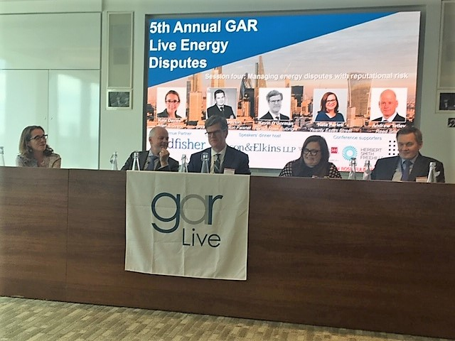 Photo of panel of people sitting and speaking at the GAR Live seminar event in London on Energy imputes. 5 speakers dressed in suits with a mix of men and women