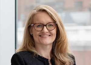 Head shot of Augusta Business women dressed in formal dress Chief Operating Officer COO Polly Bahl standing and posing for photo with a smile in bright modern London office room next to wide and floor to ceiling windows