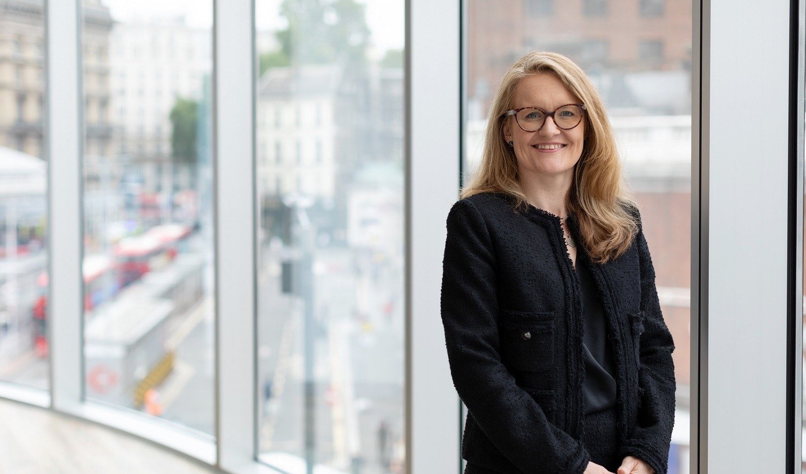 Augusta Business women dressed in formal dress Chief Operating Officer COO Polly Bahl standing and posing for photo with a smile in bright modern London office room next to wide and floor to ceiling windows