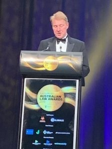 Managing director and founding partner Neill Brennan standing at the podium speaking to crowd of business people at awards event