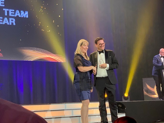 CEO Mira Brennan presenting award to winning law firm on stage at the Australian awards show