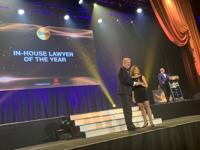 Managing director and founding partner Neill Brennan presenting award to winning law firm on stage at the Australian awards show