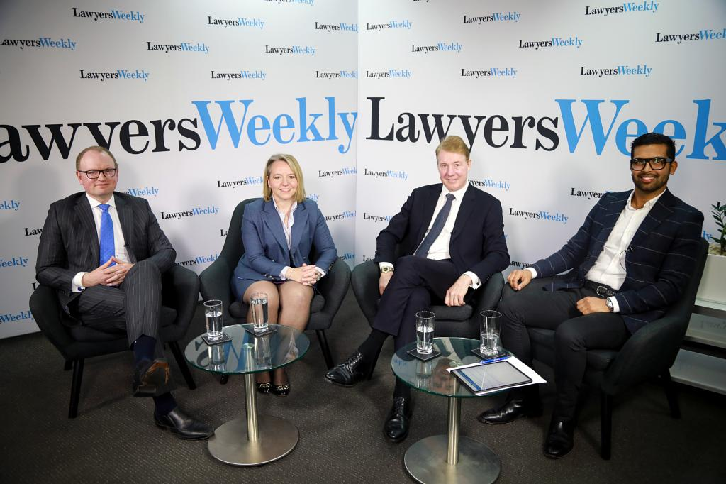 4 business people sitting side by side, facing direct to camera and posing for photo with press boards behind them title Lawyers weekly