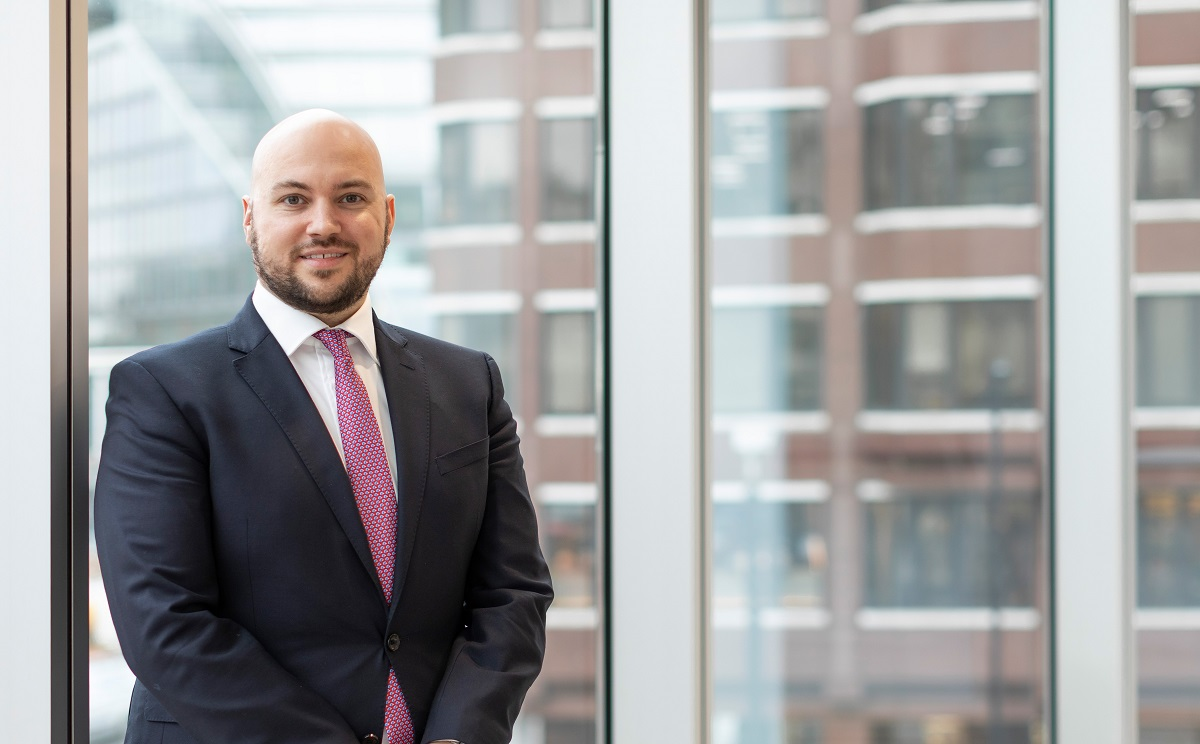 Augusta Business man dressed in suit Head of recruitment Jared Glazier standing and posing for photo in bright modern London office room next to wide and floor to ceiling windows